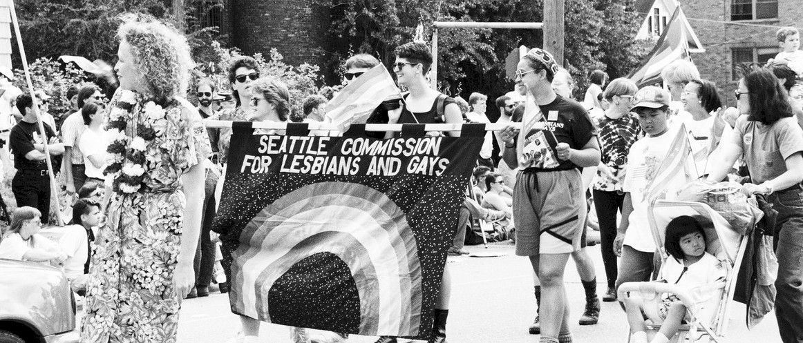 A pride parade in Seattle, WA where a sign is held that says