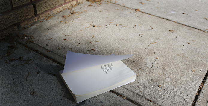 A book lies open on a sidewalk