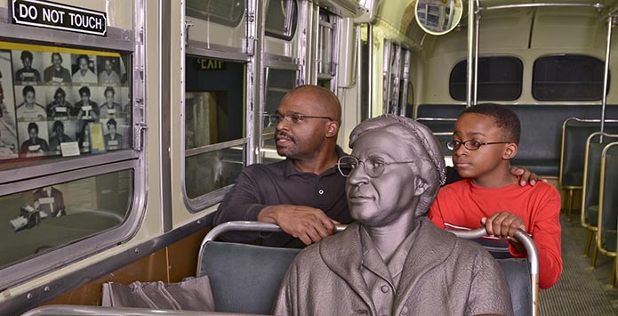 A photograph of a bus with a statue of Rosa Parks seated at the front with two black patrons seated behind the statue.