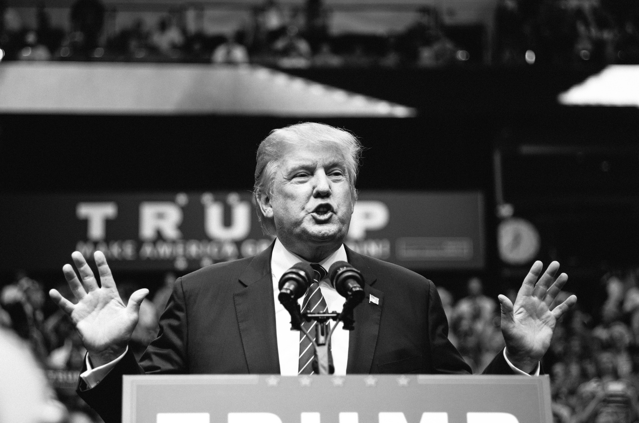 A black and white photo of Donald Trump giving a speech at a rally.