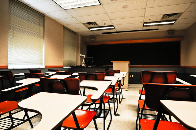 this is an image of an empty classroom with white desks and red chairs