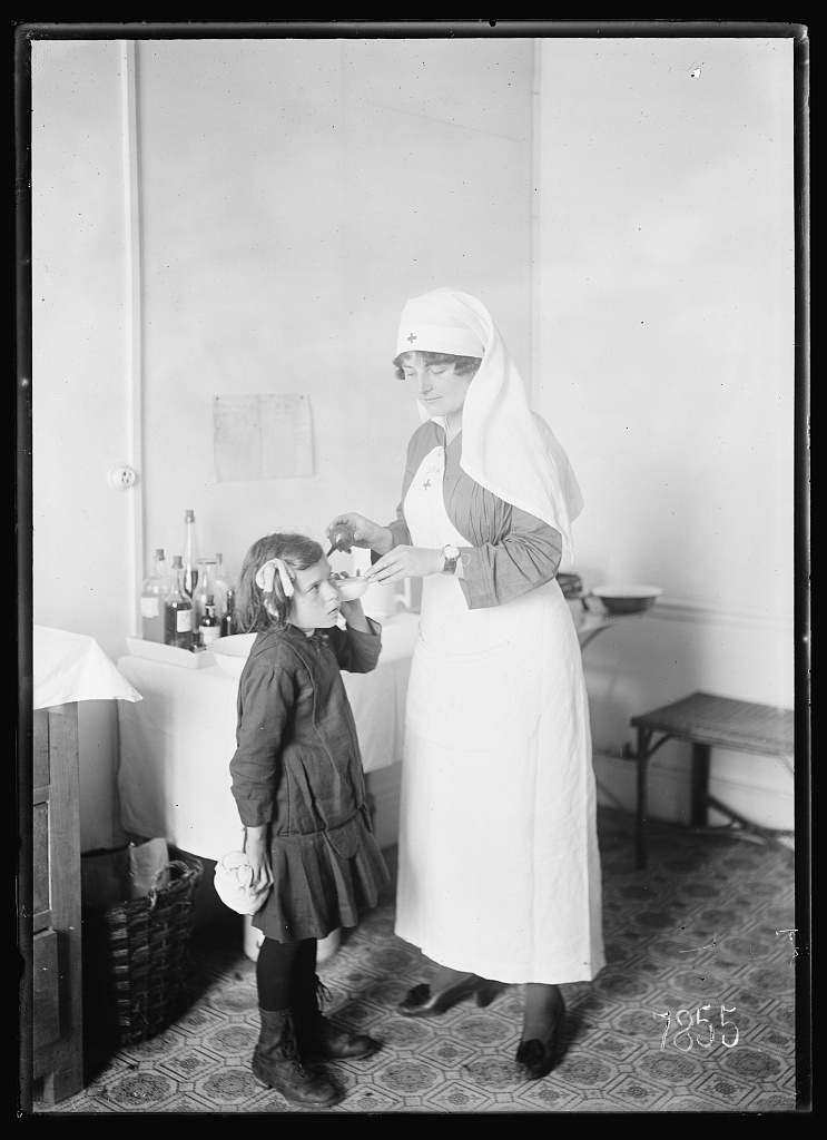 A black and white image of a Nurse treating a small child.