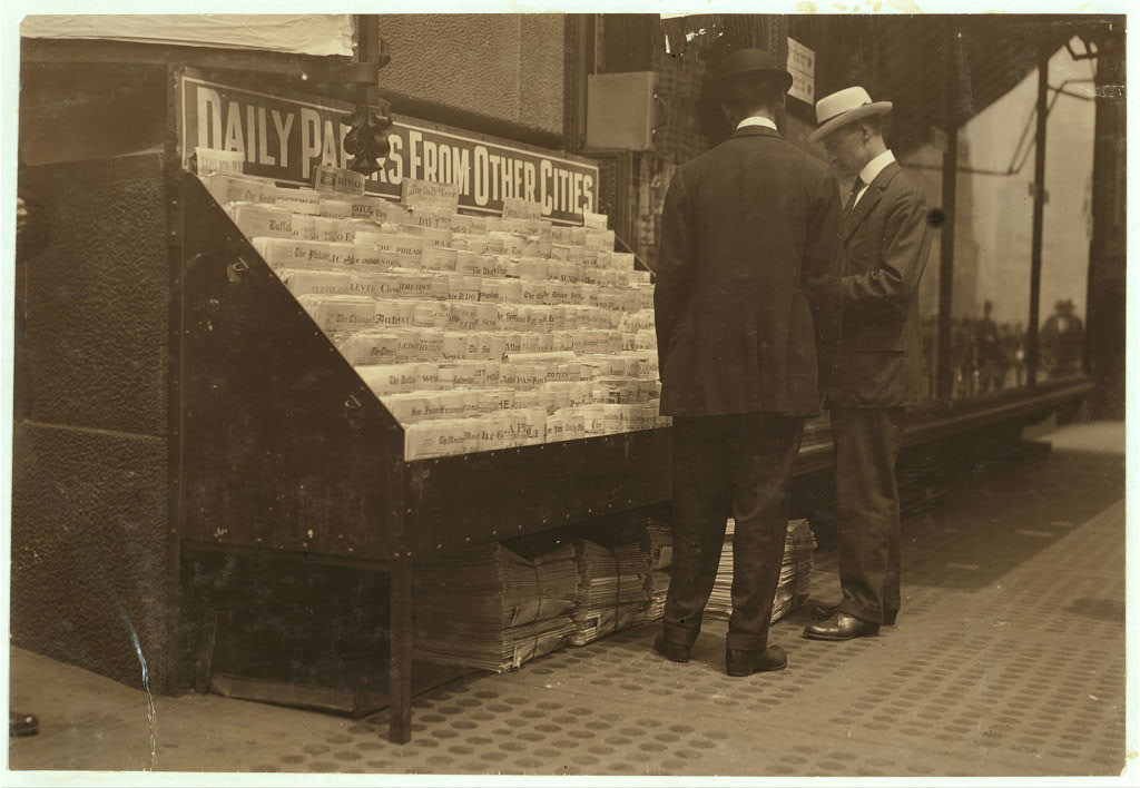 a photograph of two men standing in front of a newspaper stand that is labeled