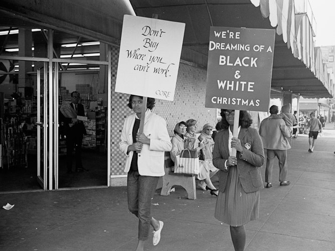 two women walk down the street holding signs that say