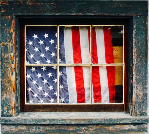 Picture of an American Flag behind a weathered window.
