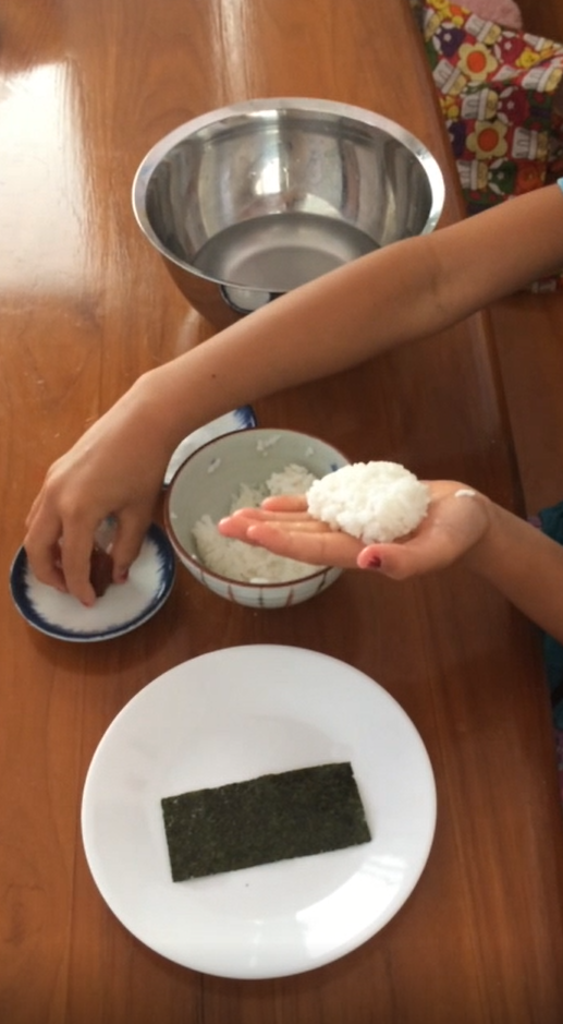 Photo 1: hands making onigiri out of rice and seaweed. Photo 2: family recipe on an old note card for Mochi Chi Chi Dango.