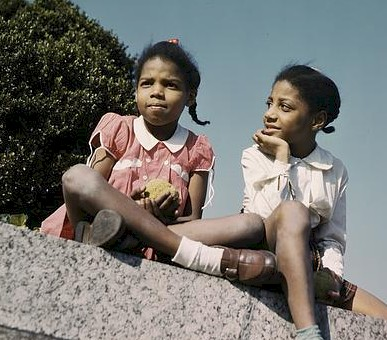 Two black girls sit on a granite bench. The girl on the left is in a pink dress and the girl on the right is in white.