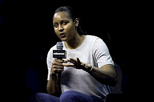 A black woman, Maya Moore, is seated, wearing a white t-shirt, holding a microphone and giving a speech.