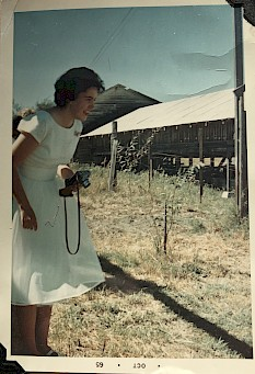 The author's mother in a white dress holding an old camera