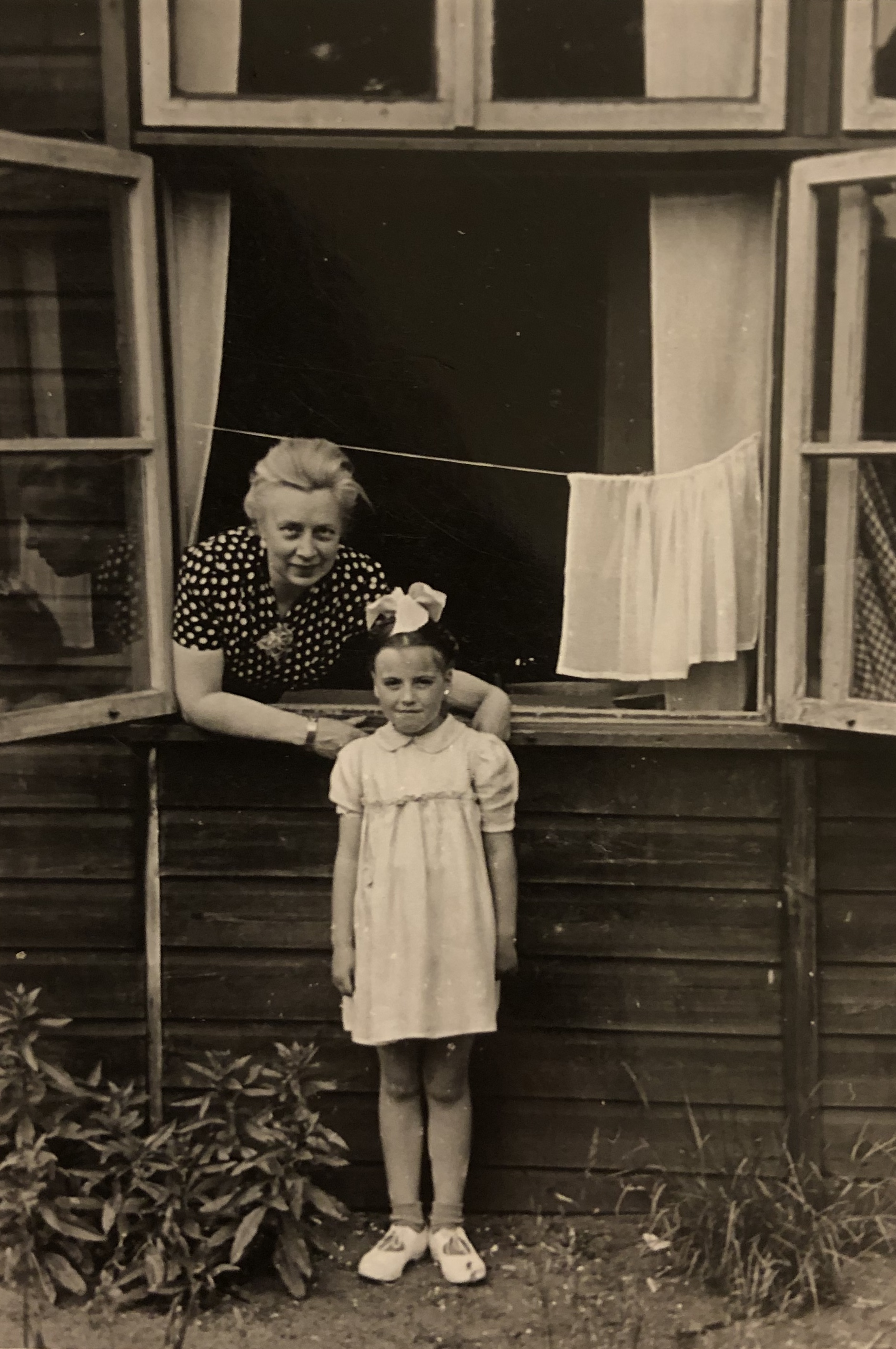 An old black and white photo of an older lady with her hands on the shoulders of a young girl.