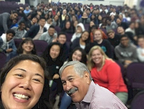 OAH Distinguished Lecturers Catherine Choy and Albert Camarillo taking a selfie with their audience in the background