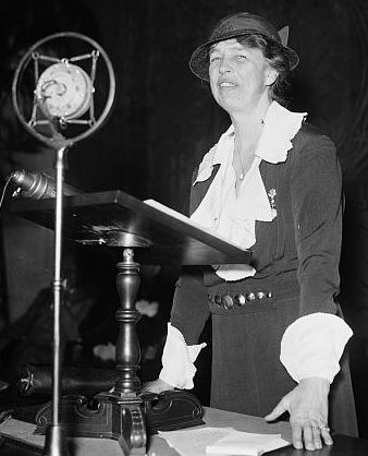 Eleanor Roosevelt standing behind a microphone and lectern