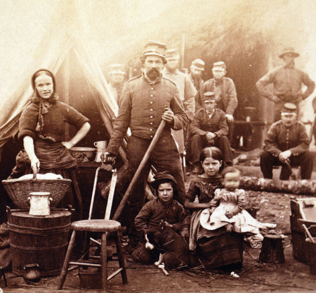 An 1861 photograph of a soldier posing with a woman and three children in a camp as more soldiers look on in the background