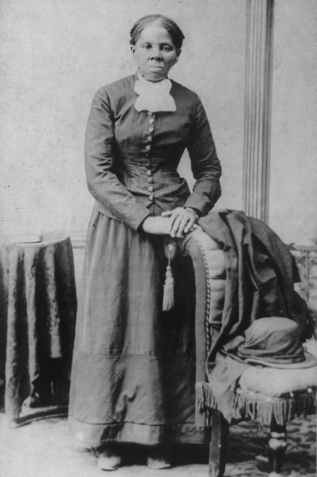 Harriet Tubman standing with one arm resting on a chair