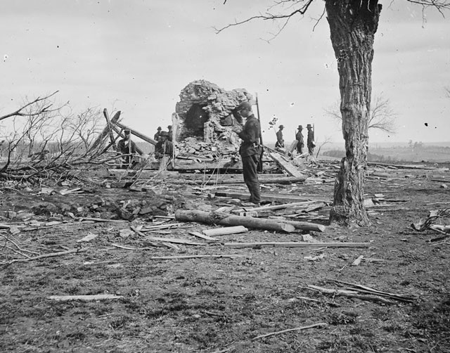 An 1862 photograph of some Civil War soldiers standing around the ruins of a house