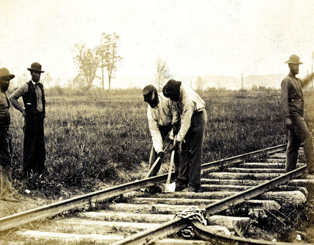 Two men working on a railroad while three other men look on