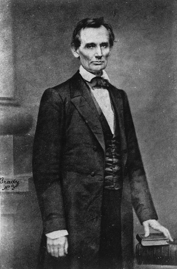 An 1860 photograph of Abraham Lincoln standing with his left hand placed on a stack of books