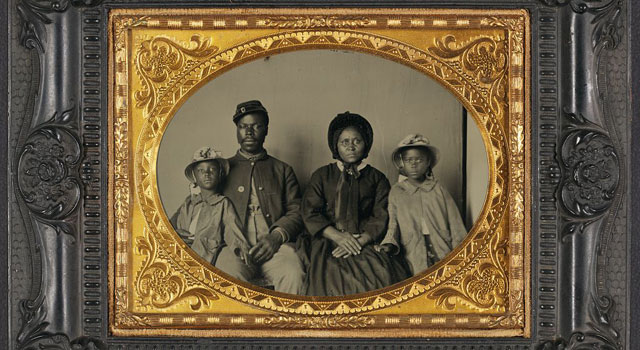 An African-American Union soldier sitting with his wife and two children