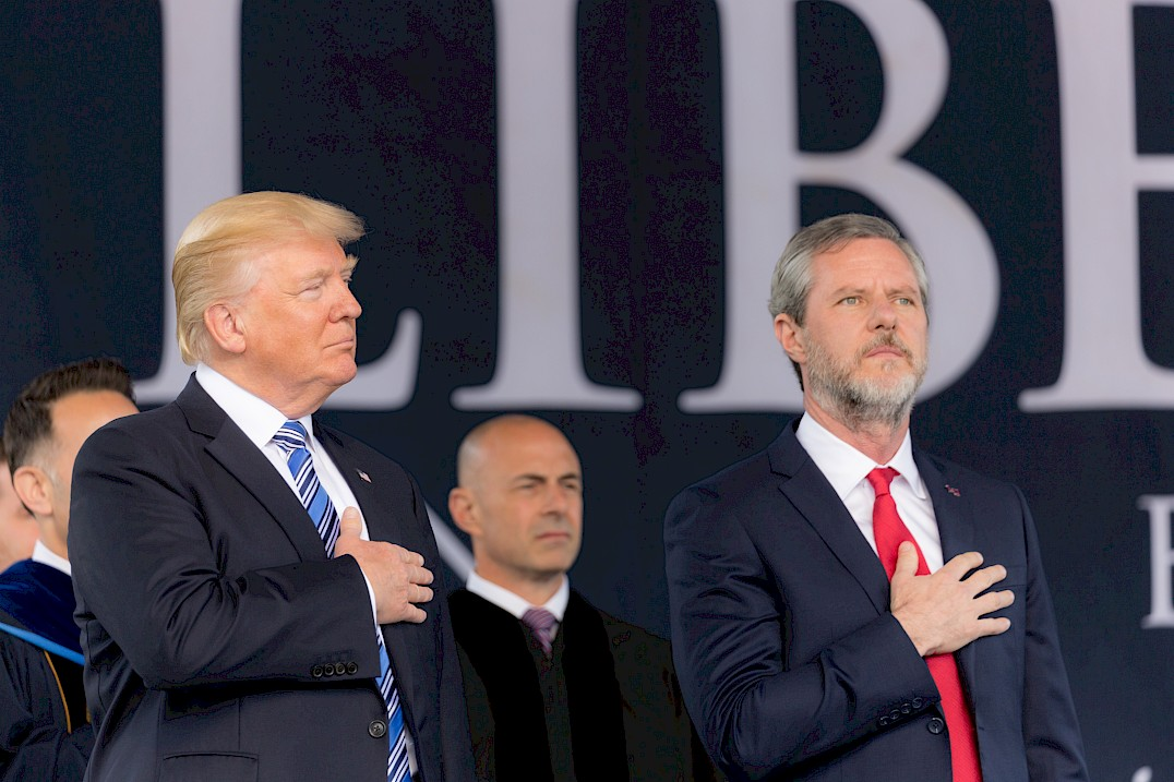 Trump with Jerry Fallwell Jr. stand with their hands over their hearts