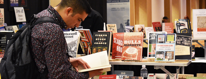 2019 OAH Annual Meeting - attendee browsing books in the exhibit hall.